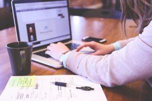 Mujer estudiando con portátil y apuntes